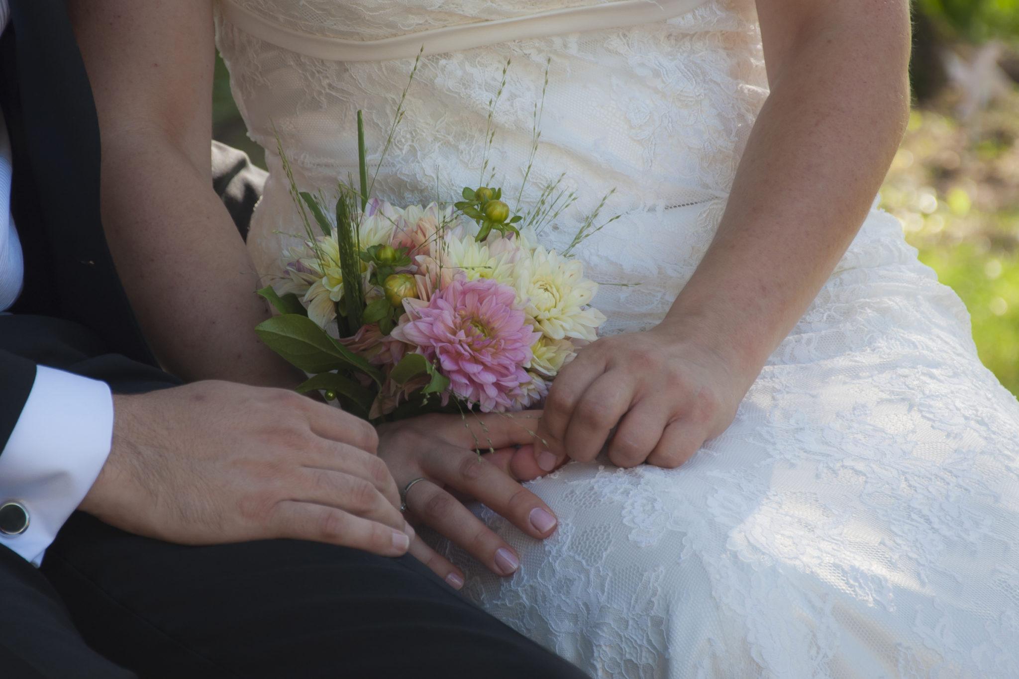 mariés se tenant la main avec bouquet