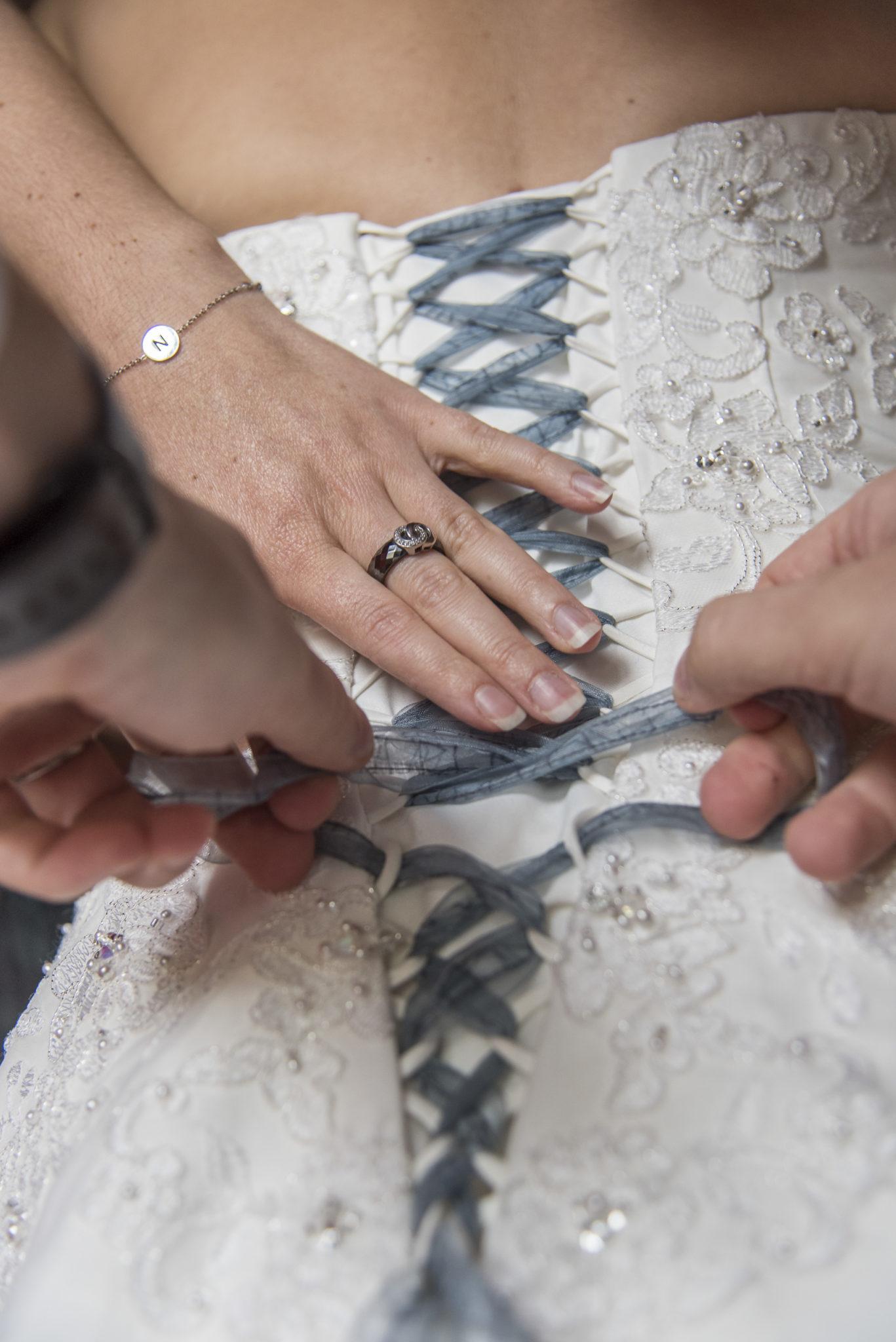 Gros plan sur le laçage de la robe de mariée par ses témoins